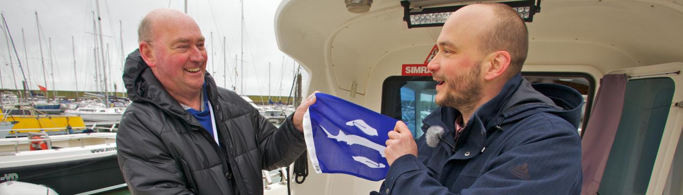 Schipper Sjef Mathijssen (links) ontvangt de eerste steurenvlag van Bram Houben van ARK Natuurontwikkeling