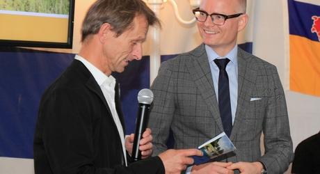 Jos Rademakers (L), directeur ARK Natuurontwikkeling, overhandigt eerste exemplaar van 'Wild, weerbaar en waterveilig' aan gedeputeerde Hubert Mackus. – foto: Ruud van Nooijen